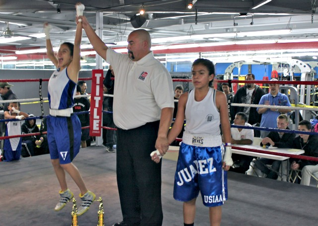 Excited about her come from behind victory over Jessica Juarez (R) on day one of the Boxers for Christ National Tournament, Stephanie Valdez jumps for joy as the judges' scores are announced.