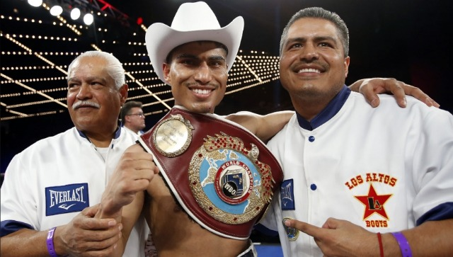 Older brother, Roberto Garcia (R) and father, Eduardo Garcia (L) join the new WBO super featherweight champion Miguel Angel Garcia in the ring after he wins the title from Orlando Salido.