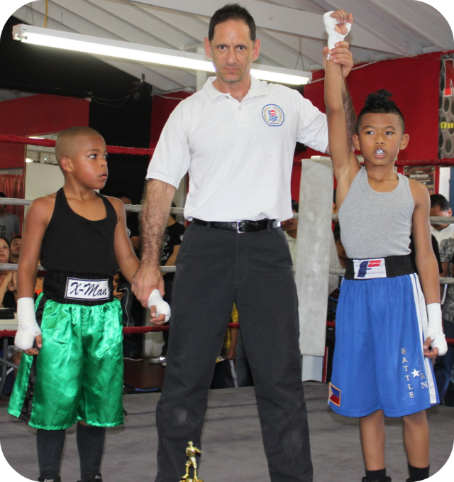 In Bout #2, it was 12 year-old Jose Chollet of Barrio Station (78.2 pounds) taking on 11 year-old Daniel Martinez of the Grace Boxing Club of Palmdale, CA (77.8 pounds). Martinez, the shorter of the two, was busier but he didn't have the same pop that Chollet exhibited. Chollet was winding up with these thunderous shots to the head and body. He even added some surprising uppercuts to his repertoire to secure this victory.