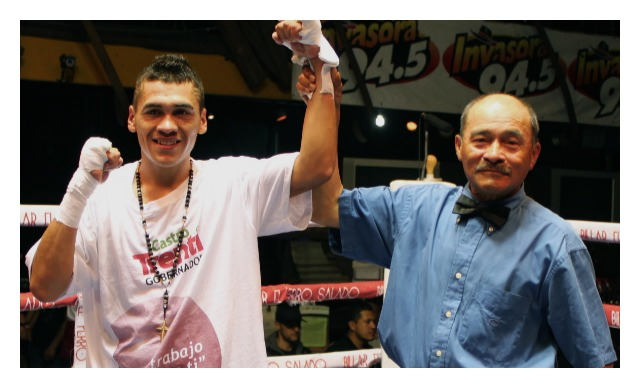"Heriberto ""Tremendo"" Delgado has his arm raised in victory by referee Juan Morales Lee."