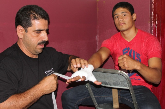 Pre-fight, Victor Fonseca (r) has his hands wrapped by his coach/manager  Luis Lorenzo.