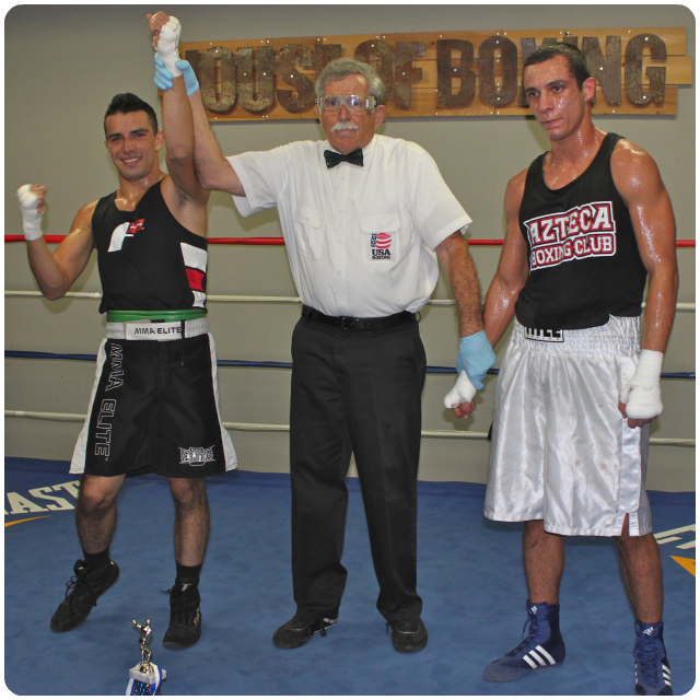 at the conclusion of Bout #3, Scott Torres of Temecula Boxing has his arm raised in victory by referee Will White over Michael Ortega