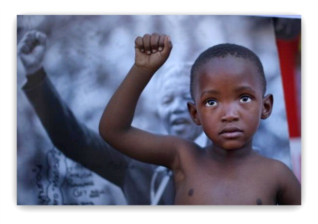 A young boy, member of the Maitibolo Cultural Dance Troop, pays his respects to Former South African President Nelson Mandela at the tribute wall outside the Medi-Clinic Heart Hospital on July 14, 2013 in Pretoria, South Africa. Photo: Christopher Furlong/Getty Images
