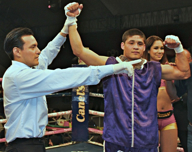 "At the conclusion of Bout #5, Victor ""Sina"" Fonseca has his arm raised in victory by referee Cristian Curiel."