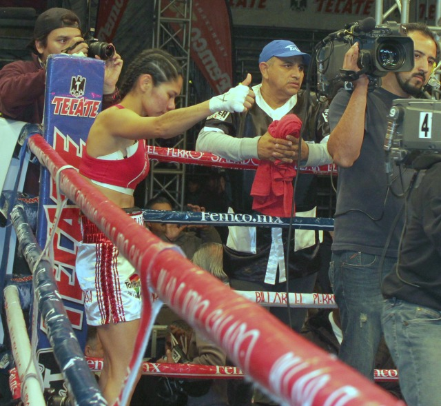 While the ring announcer announces Kenia Enriquez's victory, Selen Lopez appears to be giving her opponent the thumbs up acknowledgement.