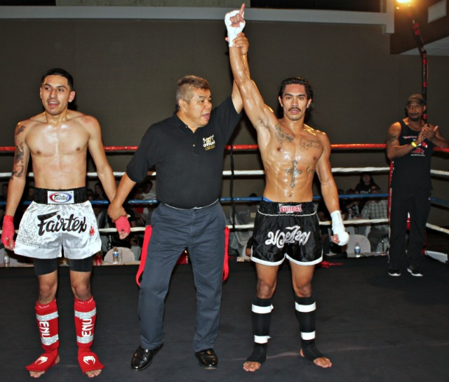"At the conclusion of Bout #3 versus Christian Rivera (l), Allan Gabriel (r) has his arm raised in victory by referee Vichai ""Rex"" Supkitpol."