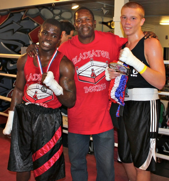 At the conclusion of his bout, the victorious Tyler Herberger (r) posed for a photo with his opponent Contravis Strozier and his coach.