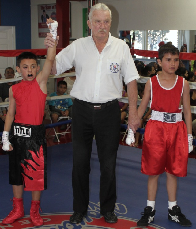 has his arm raised in victory by referee Rick Ley after he defeated the game Eddie Chollet.