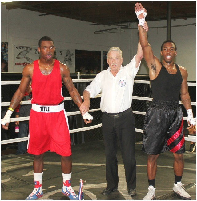 After the referee's stoppage, Robert Lutrique has his arm raised.
