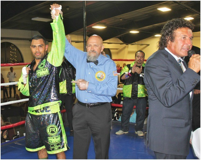 As ring announcer Benny Ricardo calls out his name, veteran referee Jose Cobian raises Roque Ramos' arm in victory.