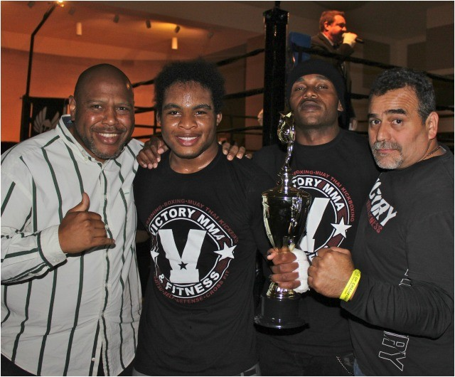 Joining John Phillips after his victory are (l to r) his proud father and equally proud coaches Steven Frye and Tony Palafox.