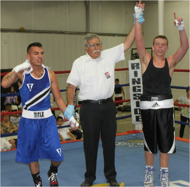 At the conclusion of Bout #1, referee Will White raises the arm of the victorious Tyler Herberger of Old School Boxing.
