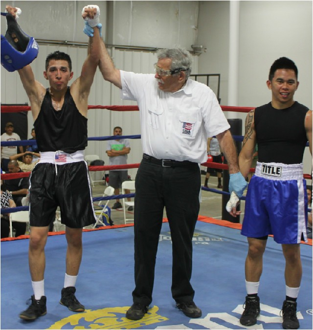 At the conclusion of Bout #2, referee Will White raises up the arm of the victorious Pedro Bernal.