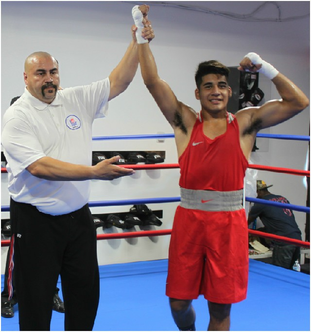 At the conclusion of Bout #4, Abraham Martinez (r) has his arm raised in victory by referee Hondo Fontan after defeating Beltran Villa of Pacheco Boxing (l).