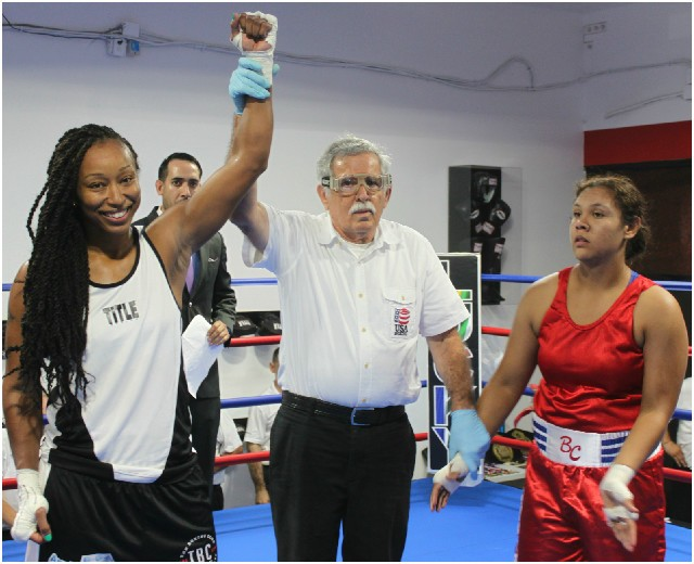 At the conclusion of Bout #6, Ophelia Hernandez (r) of the boxing club had her arm raised in victory by referee Will White after she defeated Aleisha Tosh.