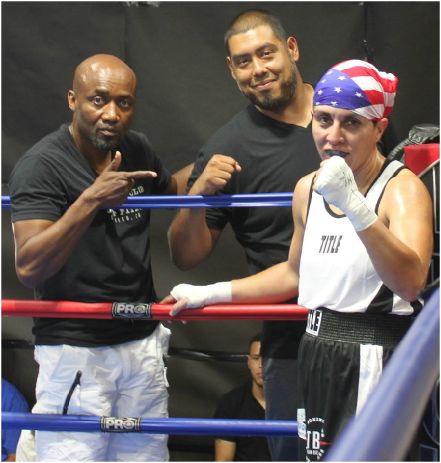 Ophelia Hernandez (r) of the boxing club had her arm raised in victory by referee Will White after she defeated Aleisha Tosh.