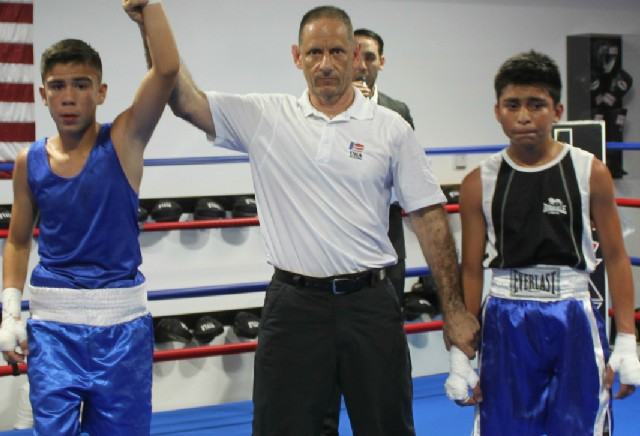At the conclusion of Bout #8, we see referee Dana Kaplan raising the arm of the victorious Ayon Sanchez of Pacheco Boxing.