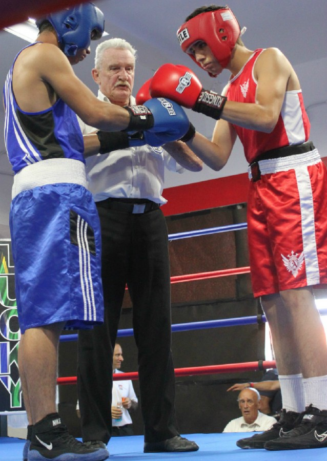 Boxers Daniel Castellanos and Ulises Bastida meet in the center of the ring.