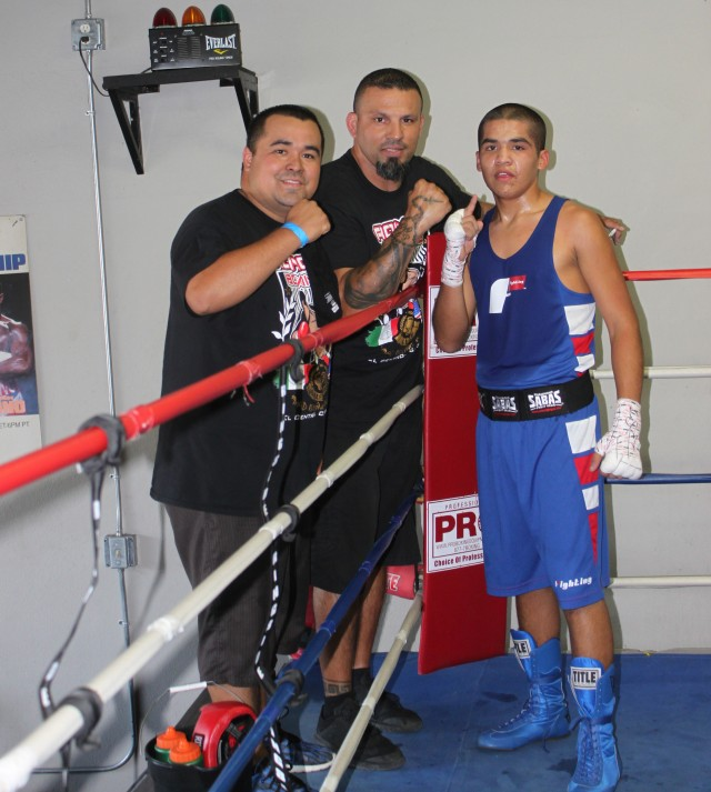 Rene Martinez and his two proud coaches pose for one last photo before Martinez leaves the ring.