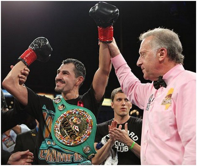 Viktor Postol has his arm raised in victory by referee Jack Reiss.
