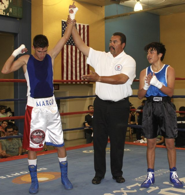 At the conclusionof their contest, we see Mario Trinidad having his arm raised in victory by referee Hondo Fontan.