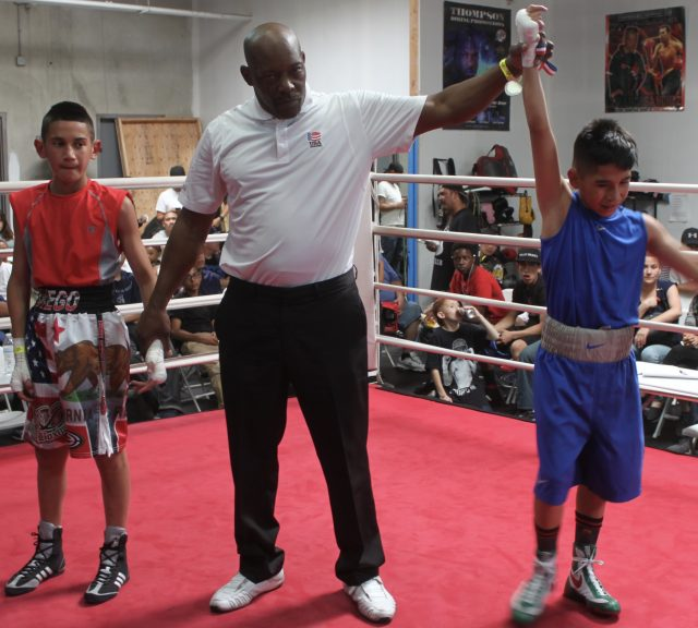 At the conclusion of Bout #5, we see referee Gerald Cheatham raising the arm of the victorious Art Barrera.