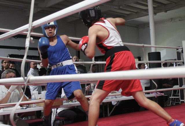 Andrew Sandoval (blue trunks) prepares Carlos Sanchez (red trunks)