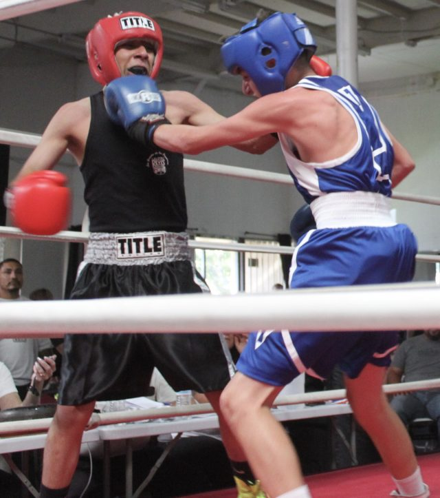 Throughout this bout, there were a great many momentum swings. In this photo both young men are landing blows at the same time.