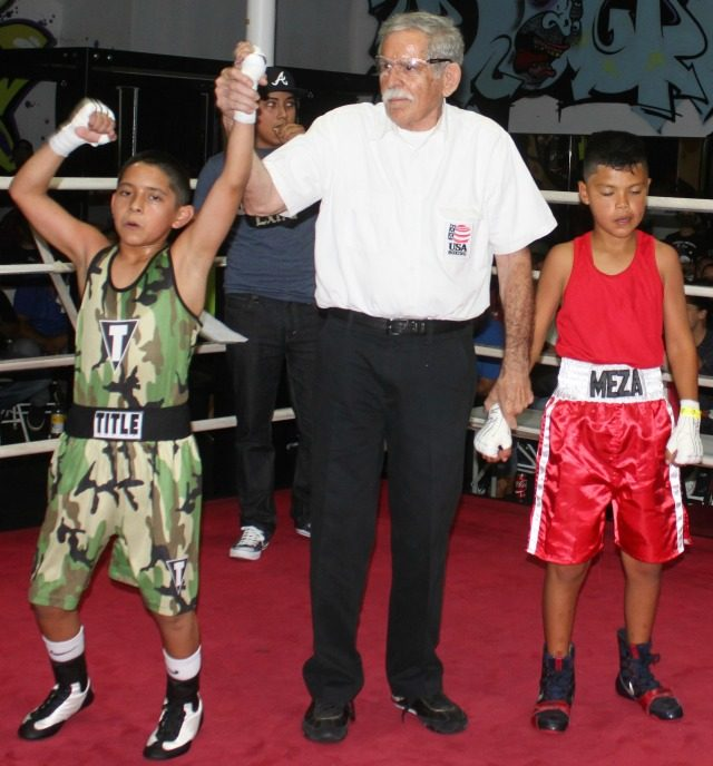 At the conclusion of Bout #3, referee Will White raises the arm of the victorious Isaiah Bernal of Romo's Boxing, Calexico, Calif.