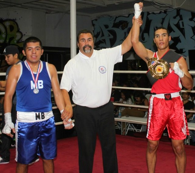 At the conclusion of Bout #12 we see referee Hondo Fontane raising the arm of the victorious David Gates after he was awarded the victory over Luis Tapia.